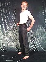 Brunette boy hand jiving in black background room